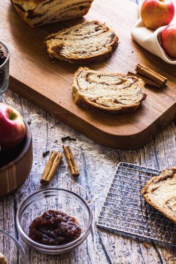 backlit shot of apple butter babka bread load and slices of wooden tray