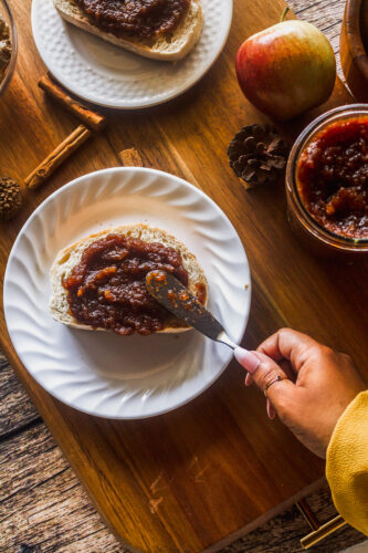 a brown hand spreads apple butter onto toast sitting on a wooden platter