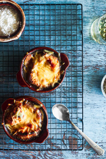 overhead shot of two oven safe french onion soup crocks filled with soup and bread covered in cheese on a wire rack on blue wood