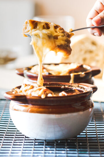 a spoonful of bread and cheese pulled from a bowl of traditional French onion soup