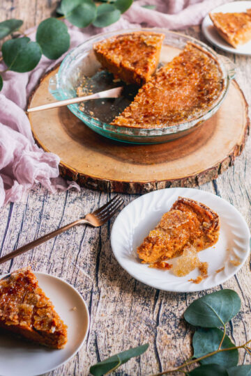 a bourbon sweet potato pie in a pie dish sitting on a piece of wood with slices of pie cut and served on plates