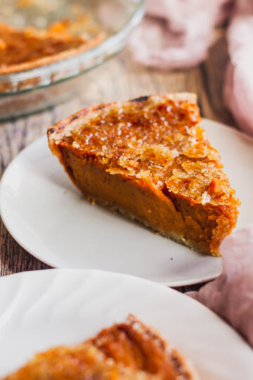 a close up side view of a slice of bourbon sweet potato pie with a caramelized sugar topping
