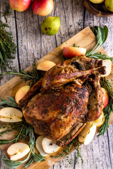 a Thanksgiving turkey on a wood platter with herbs, apples, pears