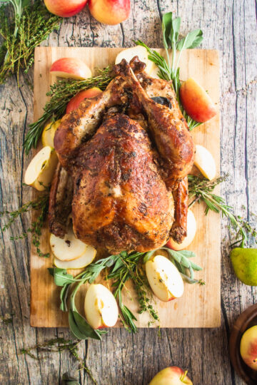 overhead shot of Thanksgiving turkey cooked in the oven, resting on a platter with aromatics and fruit