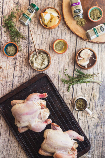 overhead shot of raw cornish hens with other ingredients like herbed butter, apples, garlic, fresh herbs and The Spice Hunter dried herbs