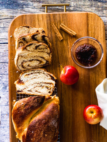 overhead shot of many slices of babka with loaf and apple butter and apples on tray