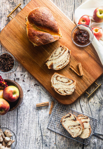overhead shot of a loaf of babka sliced on a wooden tray, with apples, apple butter, and cinnamon on the tray