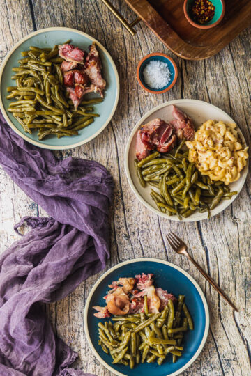 three plates of slow cooked green beans with ham hocks and mac and cheese on a wood table