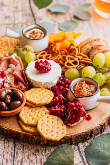 a charcuterie and cheese board with honey, grapes, almonds, slices of bread, pretzels, cheeses, meats, and fresh fruit