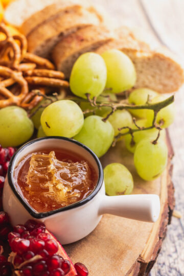 close up of honey in a bowl with honeycomb, and grapes and pomegranate on a wood board