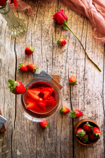overhead shot of a love martini copycat of the melting pot  with a bowl of strawberries