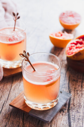 two glasses of paloma sit on coasters with juiced grapefruits behind them