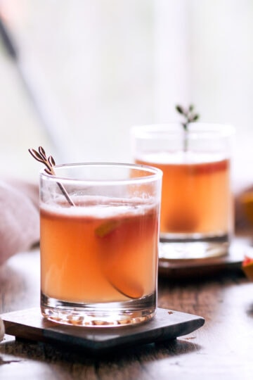 backlit photo of two glasses filled with easy paloma recipe with spoons