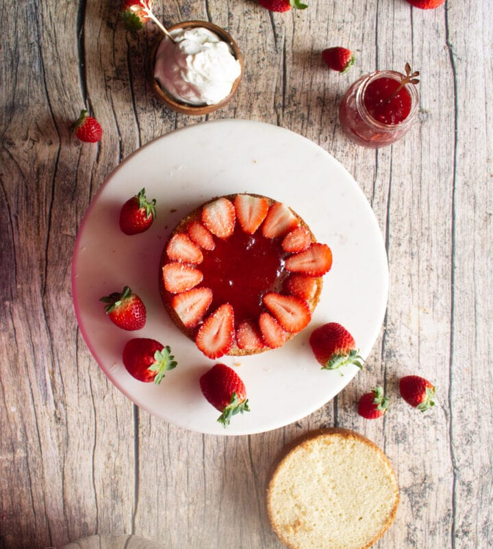 an overhead view of a layer of cake being topped with strawberry filling and fresh sliced strawberries