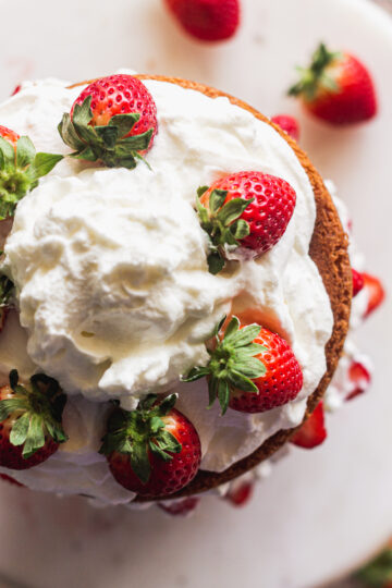 the top view of the layered strawberry cake with strawberries on top of the whipped cream topping in a pattern