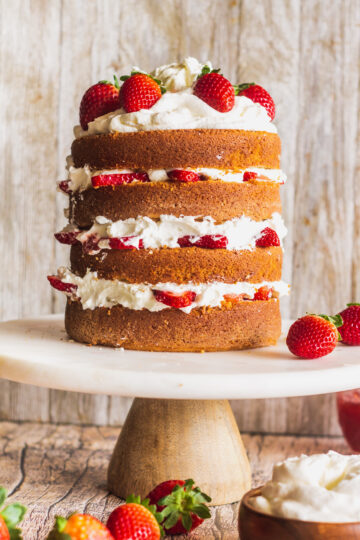 a side view of the height of the multi-layered strawberry shortcake cake on a cake stand