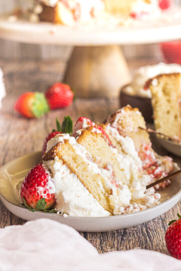 a side view of a slice of strawberry shortcake cake topped with a whole strawberry