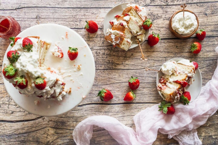 overhead shot of a strawberry chantilly cake being served with extra whipped cream and strawberries