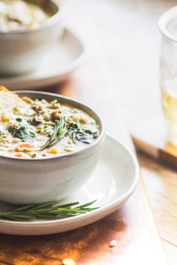 a side view of a bowl of chicken and wild rice soup with rosemary sprigs and crusty bread in the bowl